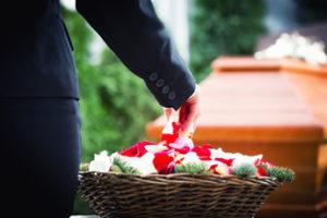 Trauerfloristik: Blütenblätter werden ins Grab gestreut