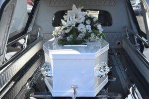Bestattungskosten: Leichenwagen mit geschmücktem Sarg