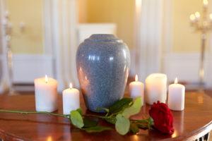 Schmuckurne umgeben von Kerzen und einer Rose