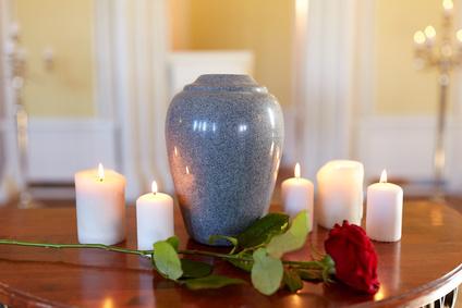 Feuerbestattung: Schmuckurne umgeben von Kerzen und einer Rose