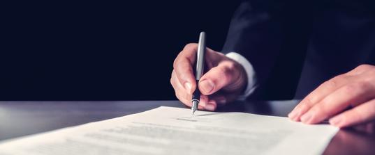 Ein Mann unterzeichnet ein Dokument