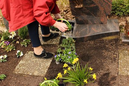 Kosten einer Erdbestattung: Ältere Frau pflanzt Blumen auf einem Grab