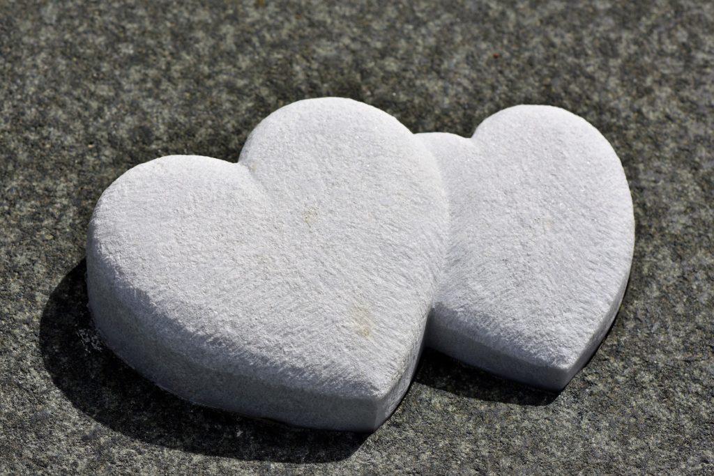 Motiv für eine Trauerkarte: Zwei verschmolzene Herzen aus Stein