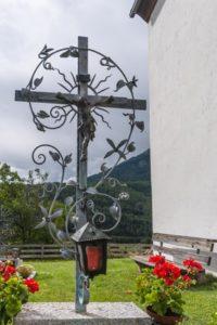 Kunstvolles Grabkreuz aus Schmiedeeisen mit Blumen und Laterne