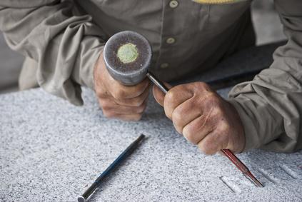 Grabplatten: Steinmetz bearbeitet ein Grabmal