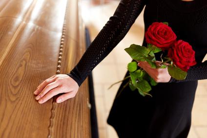 Trauerhilfe: Frau mit Trauerkleid auf einer Beerdigung
