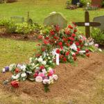 Bestattungsarten: Frisches Grab mit Blumenschmuck
