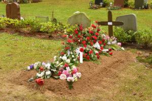 Friedhofsgärtnerei: Frisches Grab mit Blumenschmuck
