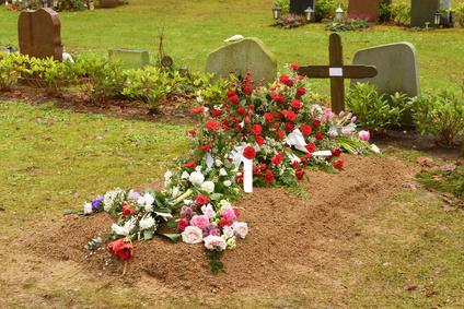Frisches Grab mit Trauerkranz und Blumenschmuck