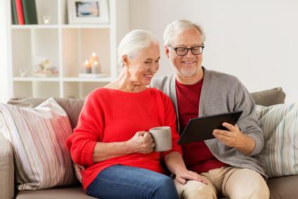 ÄLteres Ehepaar sitzt auf dem Sofa und informiert sich mit einem Tablet-PC