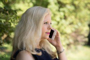Trauerhilfe und Trauerbewältigung: Frau in schwarzem Kleid hält ein Mobiltelefon ans Ohr