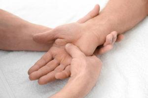 Leichenstarre: Ein Bestatter massiert die Hand eines Verstorbenen