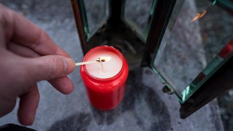 Grabschmuck: Grablicht wird entzündet und in Grablaterne gestellt