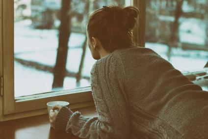 Trauernde Frau am Fenster