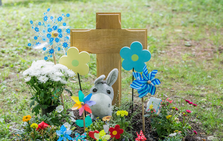 Grabkreuze: Urnenkreuz auf einem Kindergrab