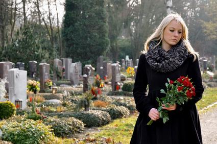 Ablauf einer Beerdigung: Junge Frau trauert auf Friedhof