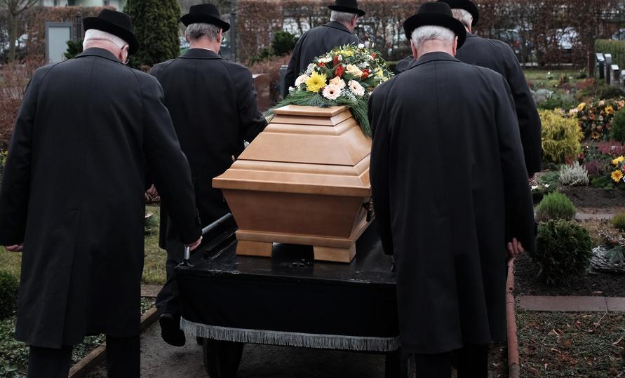 Ablauf einer Beerdigung: Sargträger tragen einen Sarg